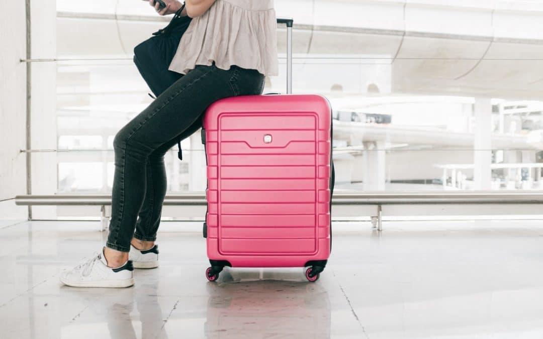 personne assise sur sa valise a l'aéroport en attendant son taxi aéroport