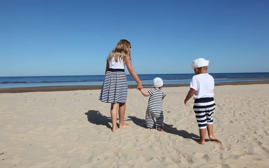 enfants sur la plage avec de parents qui ont décider de voyager avec des enfants